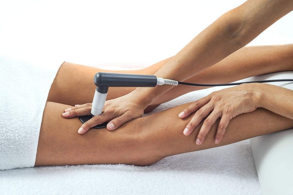 Patient receiving treatment for knee pain from a TECAR therapy machine