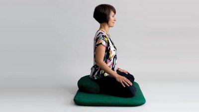 Woman sitting meditating with good posture